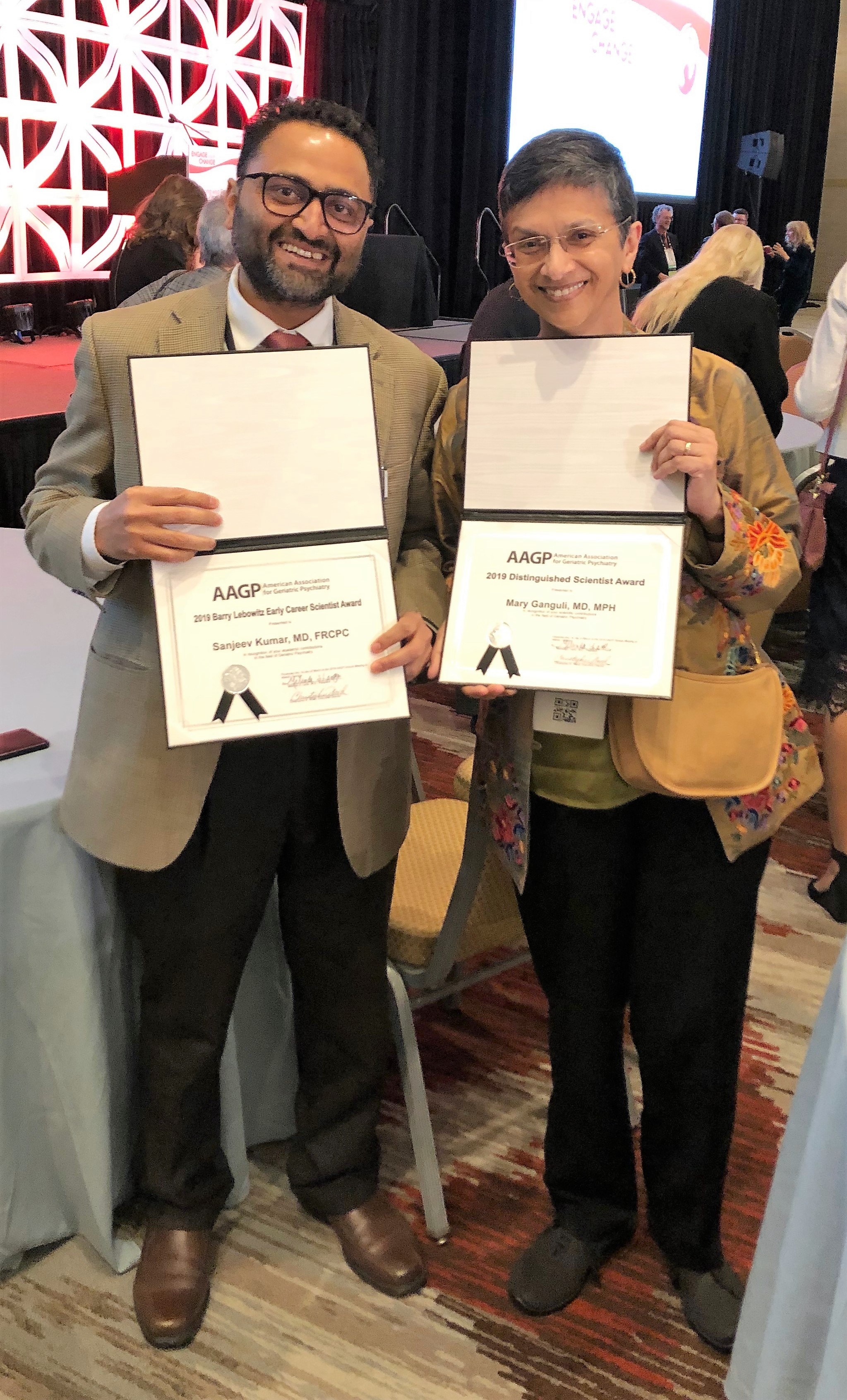 Drs. Sanjay Kumar and Mary Ganguli display their 2019 AAGP Awards